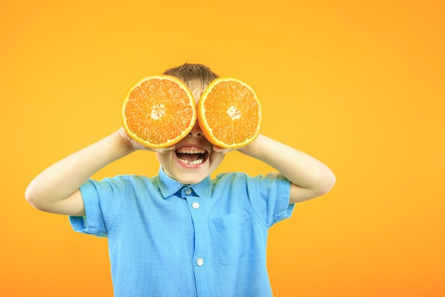 Happy cute boy is having fun played with fruit orange on yellow background wall.