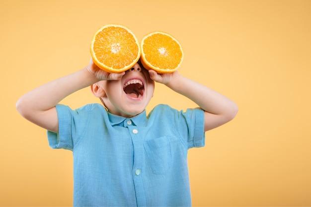 행복 한 귀여운 소년 재미 과일 오렌지와 함께 연주