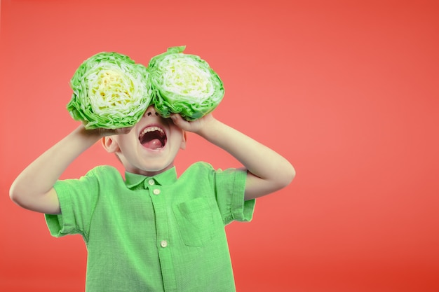 Happy cute boy is having fun played with green cabbage on pink background wall.