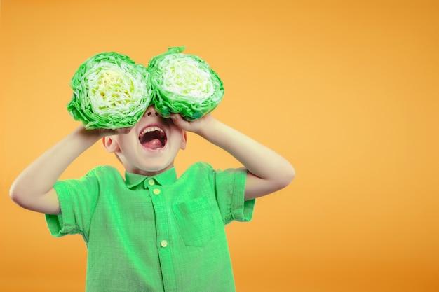 Счастливый милый мальчик весело играет с зеленой капустой