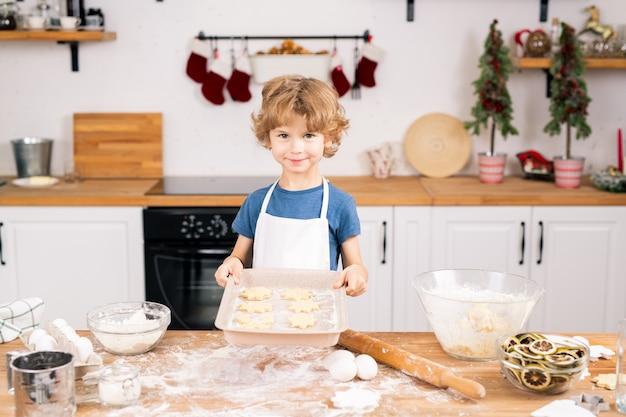 台所のテーブルのそばに立っている間あなたを見ている生の自作のクッキーを持つ幸せなかわいい男の子
