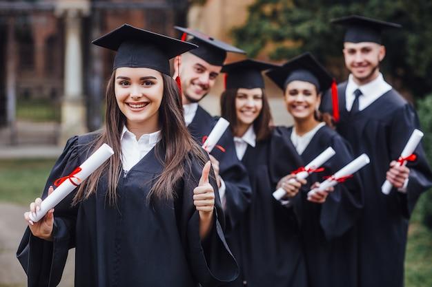 Счастливая милая брюнетка кавказская выпускница улыбается, затуманенное одноклассники позади