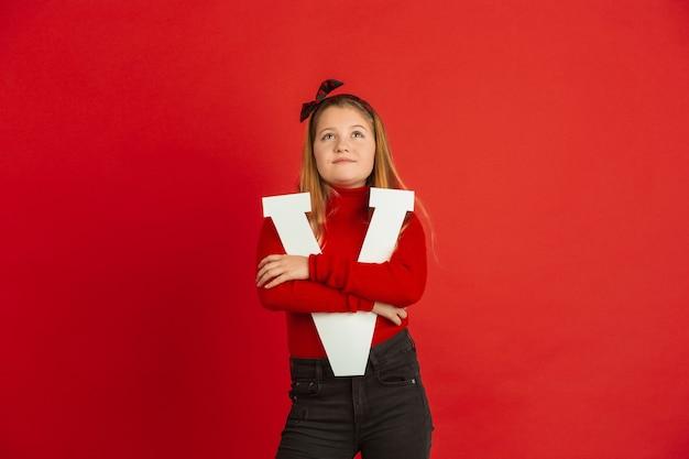 赤いスタジオの背景に手紙を保持している幸せでかわいい白人の女の子。人間の感情、顔の表情、愛、関係、ロマンチックな休日の概念。