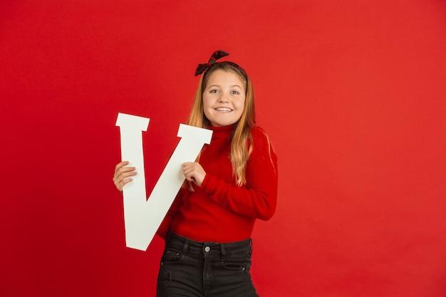 赤いスタジオで手紙を保持している幸せでかわいい白人の女の子