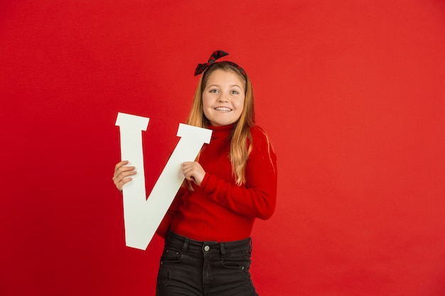 Happy, cute caucasian girl holding letter on red studio
