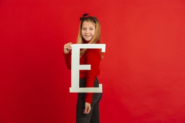 Felice, carina ragazza caucasica tenendo la lettera su studio rosso