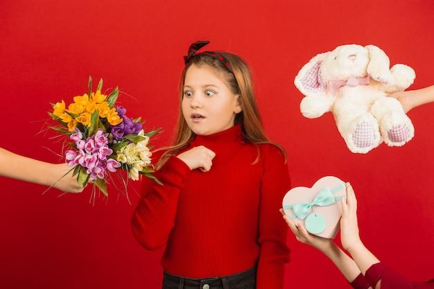 Счастливая, милая кавказская девушка изолирована на красной студии