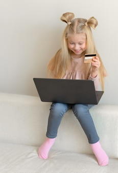 Happy cute caucasian little girl holding credit card buying online sitting on the couch