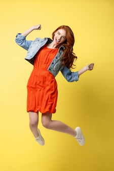 Happy cute caucasian woman is jumping up, in causal summer outfit