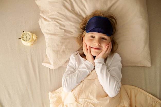 Happy cute child girl smiles and looks with a loving look, lies in the bed. joy and good morning.