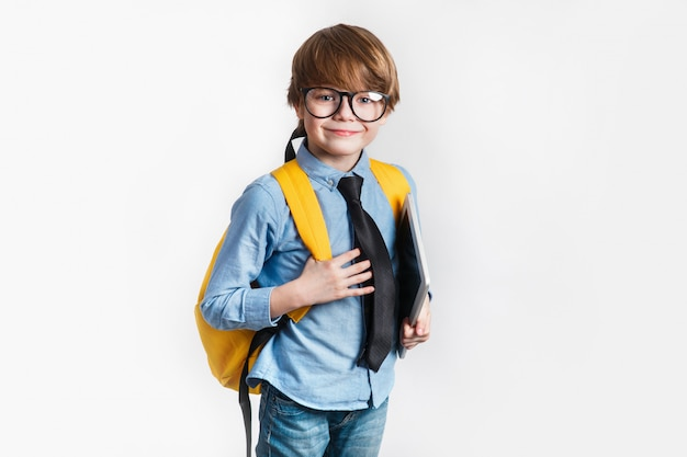 Happy cute clever boy in glasses with school bag and tablet in his hand. back to school.