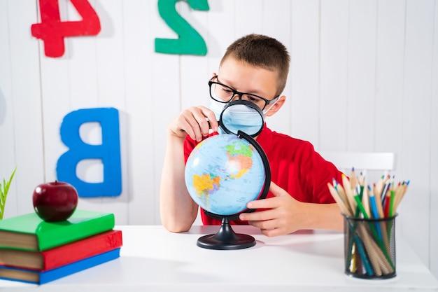 Счастливый милый умный мальчик сидит за столом в очках с поднятой рукой. ребенок готов ответить с доской