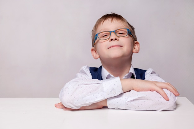 Happy cute clever boy is sitting at a desk in a glasses. child is ready to answer. ready for school. back to school.