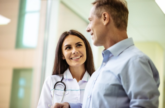 Счастливая милая уверенная в себе женщина-врач разговаривает со старшим пациентом в больнице