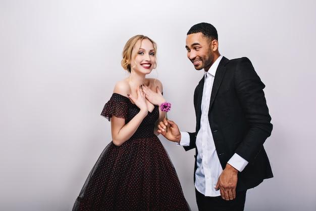 Счастливая милая влюбленная пара празднует день святого валентина. привлекательная молодая блондинка в роскошном платье, красивый мужчина в смокинге, дарит цветок, улыбается, положительные эмоции.