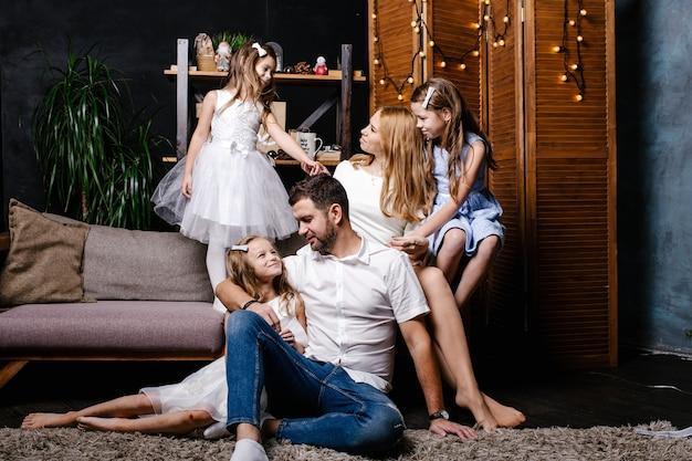 카펫에 크리스마스 트리 아래 선물을 교환하는 세 자녀와 함께 행복 한 귀여운 가족.