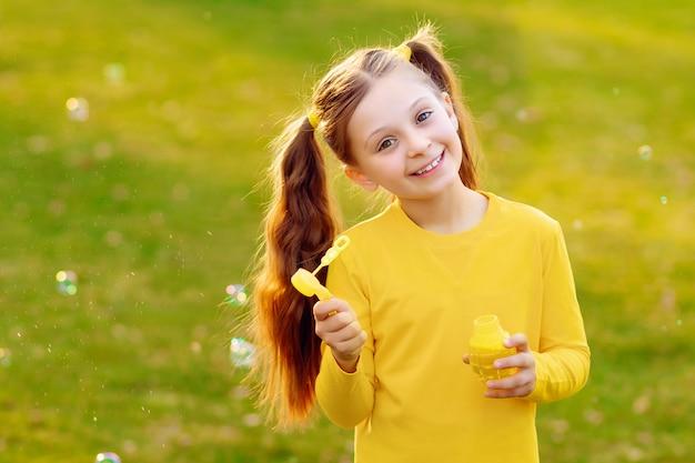 夏の公園でシャボン玉を吹く幸せなかわいい女の子。