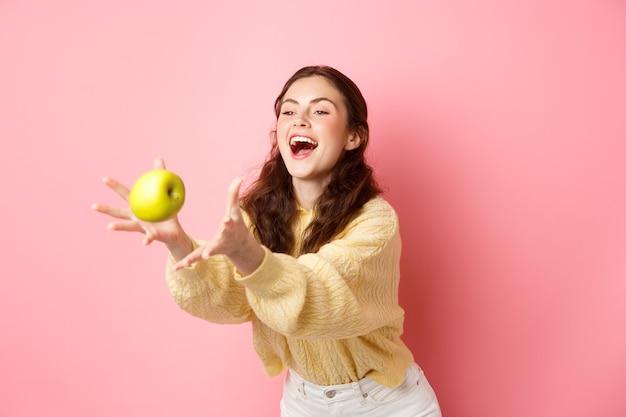 Счастливая милая девушка ловит яблоко и смеется, время для здорового обеда, наполненного фруктами, стоит у розовой стены