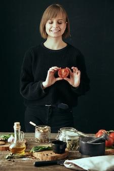 Счастливая милая девушка готовит здоровую пищу на кухне