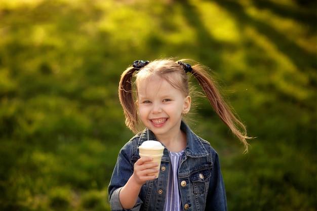 Счастливая милая девушка ест мороженое на природе в теплый летний вечер