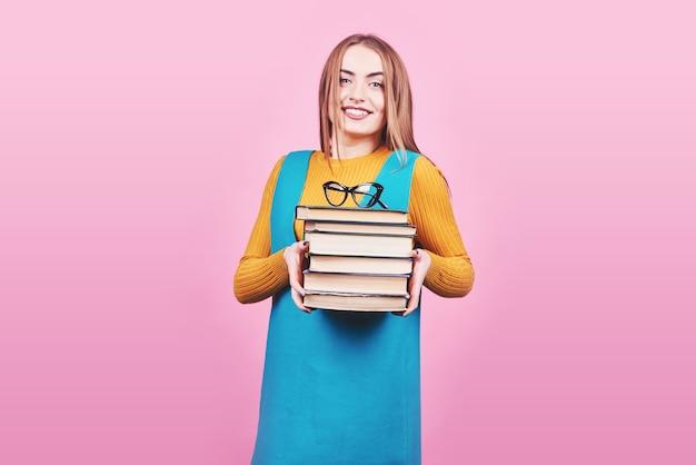 カラフルなピンクの背景に分離された本の山を手に持って幸せなかわいい女の子。