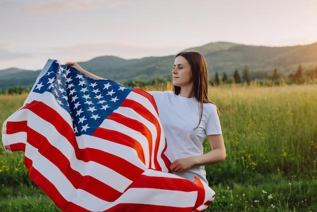 Счастливая милая девушка держит национальный флаг сша