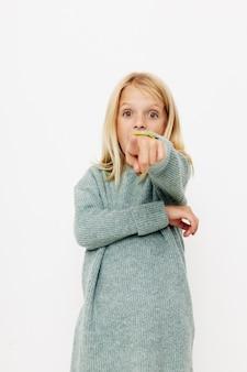 セーターの幸せなかわいい女の子は、子供のライフスタイルの概念をしかめっ面