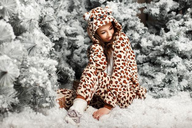 Счастливая милая девушка в модной пижаме с медведем сидит возле елки