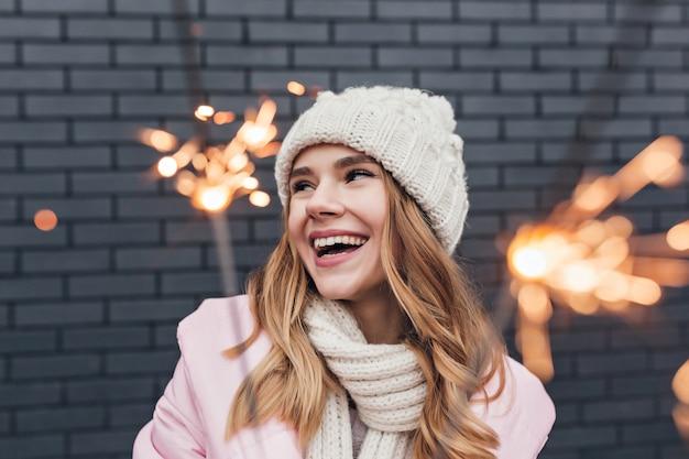 향과 함께 포즈를 취하는 겨울 모자에 행복 한 귀여운 소녀. 휴일에 재미 관심이 금발 여자의 야외 샷.