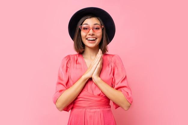 Ragazza carina felice in abito rosa in posa