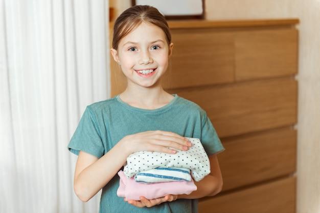 행복한 귀여운 소녀는 옷장에 물건을 정리합니다. 화려한 옷의 스택. 옷장에 옷을 정리하는 아이. 옷장에서 주문하십시오. 차일 의류와 옷장