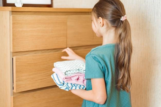 Счастливая милая девушка наводит порядок в шкафу