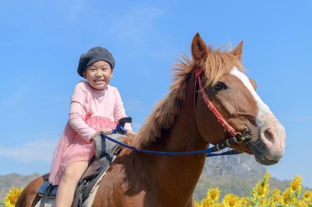 Happy cute girl riding horse in sunflower field