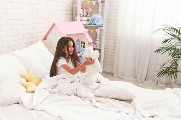 Счастливая милая девушка сидит на кровати в детской комнате и играет с мишкой