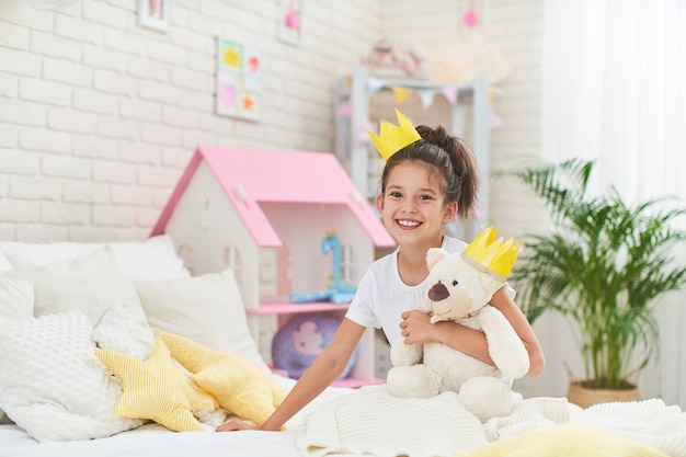 Happy cute girl sitting on the bed in her children's room and hugs teddy bear.