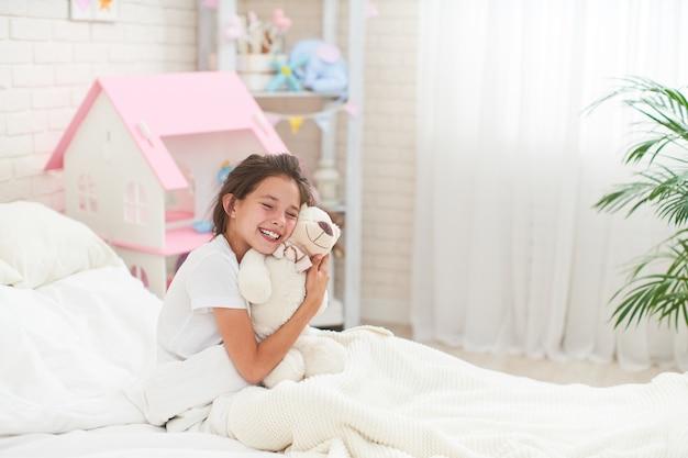 Счастливая милая девушка сидя на кровати в комнате ее детей и обнимает плюшевого медвежонка.