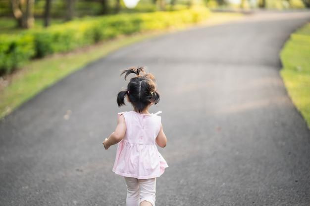 笑顔で庭で走っている幸せなかわいい女の子