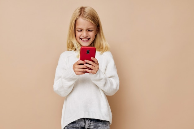 Счастливая милая девушка разговаривает по телефону на бежевом фоне