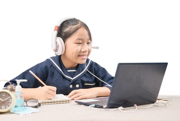 白で隔離の自宅で彼女のラップトップでオンラインストリーミングビデオを見ている幸せなかわいい女の子。ホームスクーリング、遠隔教育、新しい通常の概念