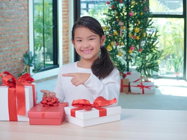 お祝いの装飾と自宅でギフトボックスを持つ幸せなかわいい女の子。