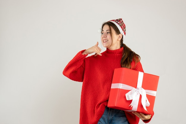 Happy cute girl with santa hat holding heavy gift making call me sign standing on white