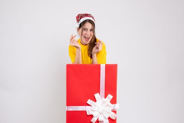白の大きなクリスマスプレゼントの後ろに立っているサンタの帽子と幸せなかわいい女の子