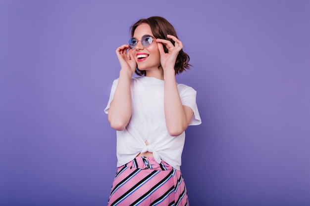 Happy cute girl with wavy hairstyle touching her glasses with smile. indoor shot of magnificent curly lady in white t-shirt posing on purple wall.