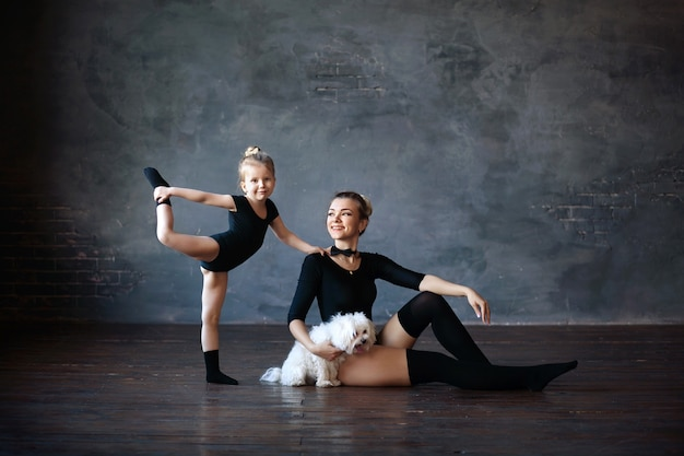 Счастливые милые гимнастки мама и дочка с белым терьером
