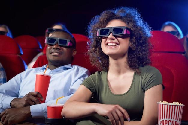 Счастливая милая пара из разных стран ест попкорн и смеется над смешной комедией в кинотеатре.