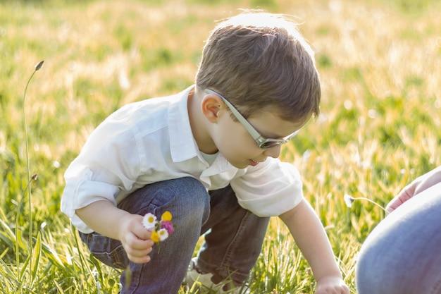 Счастливый милый ребенок собирает букет цветов в солнечном поле