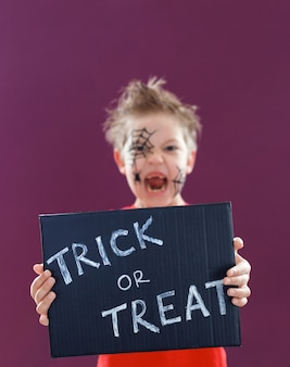 Happy cute kid with halloween makeup, holding a blackboard with the text: trick or treat. halloween concept.