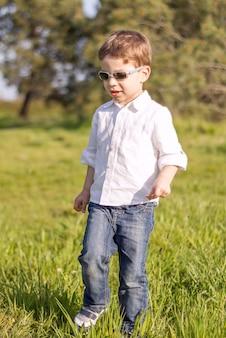 Счастливый милый ребенок в солнцезащитных очках гуляет по траве солнечного поля