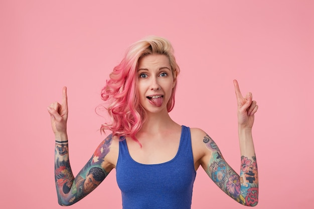 Happy cute lady with pink hair and tattooed hands, standing, wearing a blue shirt, showing tongue and fooling around. looks up and points fingers at copy space above her head.