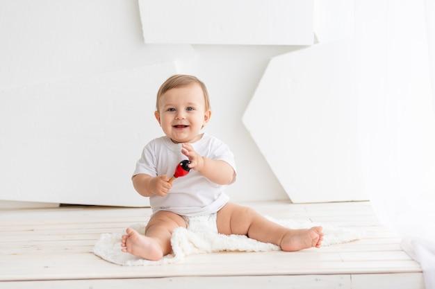 Счастливый милый маленький ребенок шести месяцев в белой футболке и подгузниках сидит на светлом фоне дома и играет, место для текста.